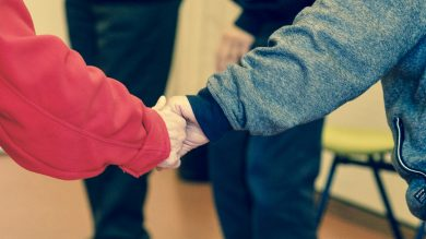 Nursing home visitor holds hand of elderly