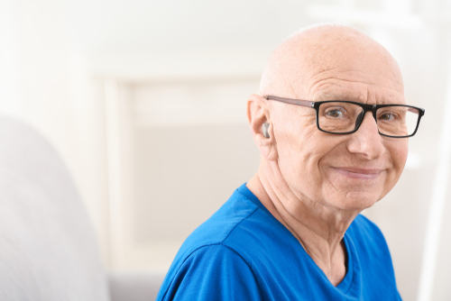 A man with a hearing aid smiling