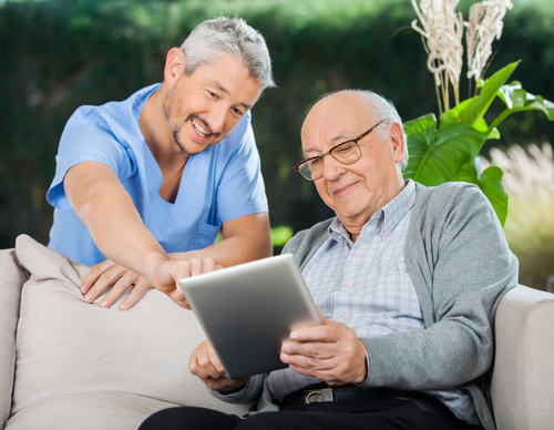 A care giver showing a senior citizen how to do something on an ipad