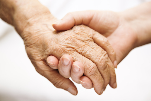 A woman holding the hand of an elderly loved one