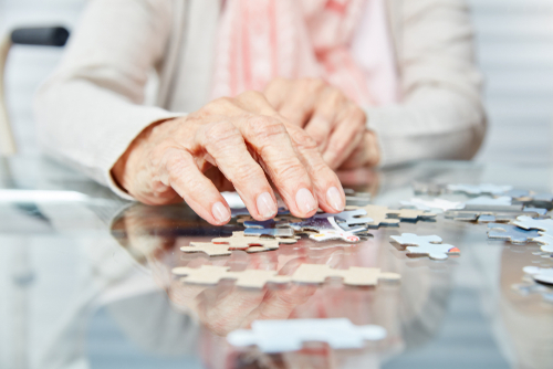 An old woman putting a puzzle together.